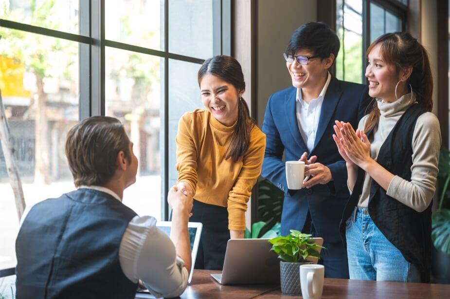Quatro pessoas em um ambiente de trabalho harmonioso, todos estão sorrindo e duas delas estão dando das mãos