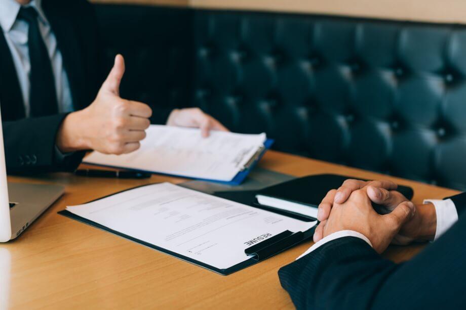 """duas pessoas sentadas à mesa em que uma está de mãos cruzadas e a outra está segurando papéis e fazendo sinal de """"legal"""" para representar um feedback"""