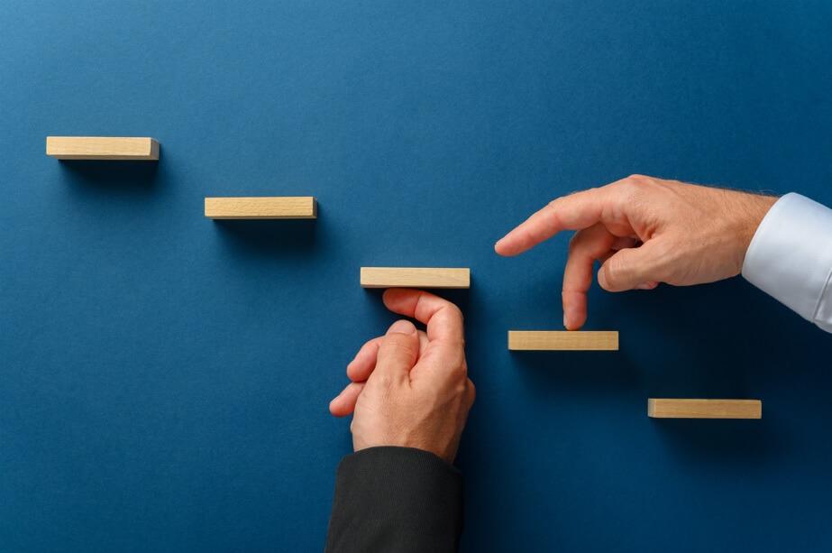 em um fundo azul aparecem dedos subindo uma pequena escada e outra uma mão sustentando um degrau em sinal de apoio profissional para conceituar o que é competência