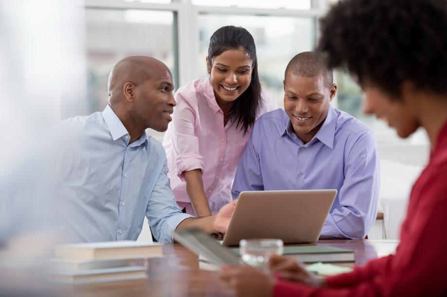 grupo de quatro executivos com características latinas, trabalhando na frente de um computador em um escritório em clima de descontração