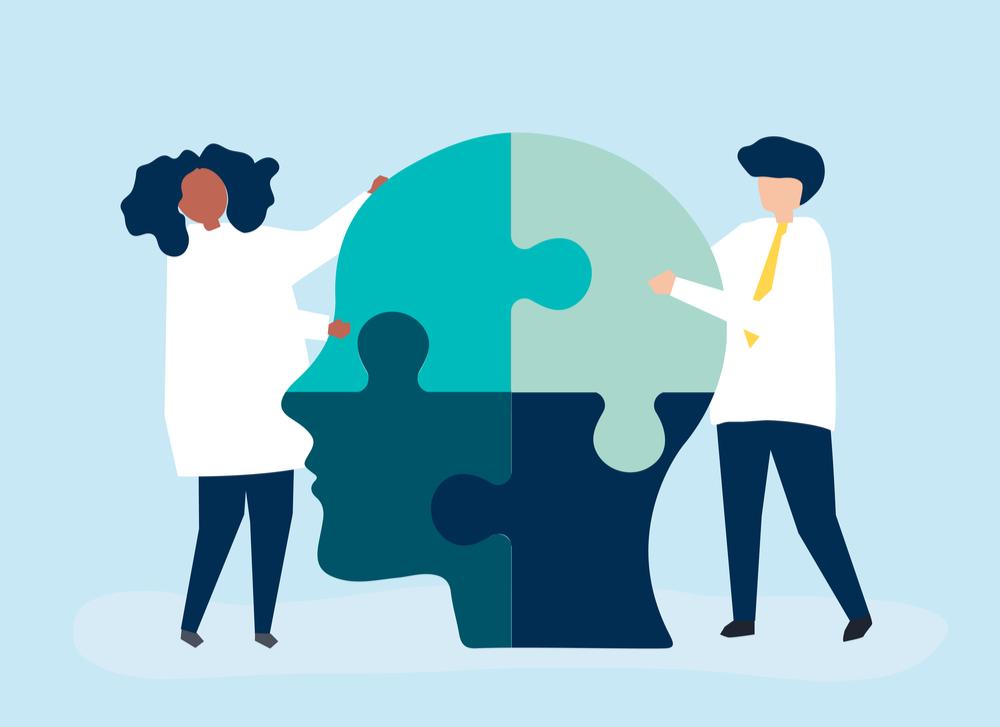 Duas pessoas montando um quebra-cabeça que forma uma cabeça, em referência à saúde mental